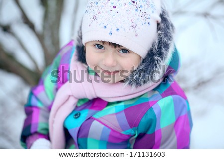 cheerful girl child in the park in winter - stock photo