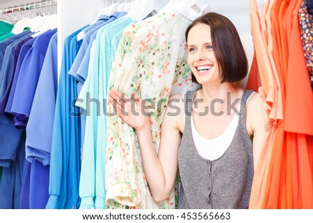 Cheerful girl choosing clothes in boutique - stock photo