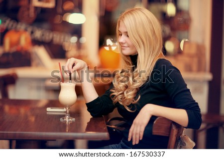 cheerful girl drinking coffee in a cafe at night - stock photo