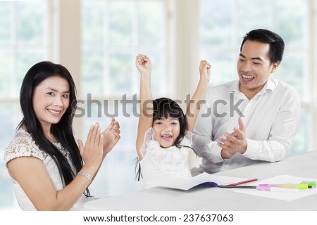 Cheerful girl finishing her homework and getting applause from her parents - stock photo
