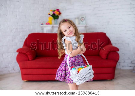 cheerful girl holding a white basket with colorful Easter eggs on red couch , the child laughs and fun - stock photo