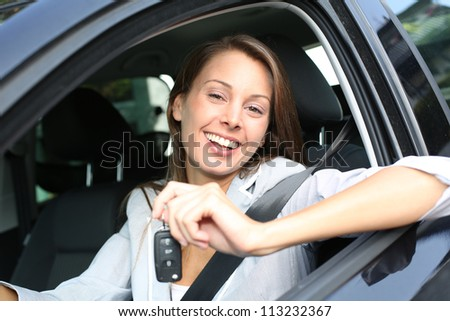 Cheerful girl holding car keys from window - stock photo