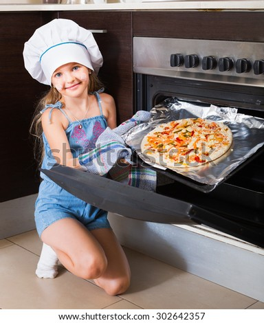 Cheerful girl in cap prepared Italian pizza at home - stock photo