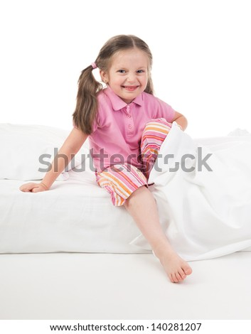 cheerful girl in pink dress on bed - stock photo