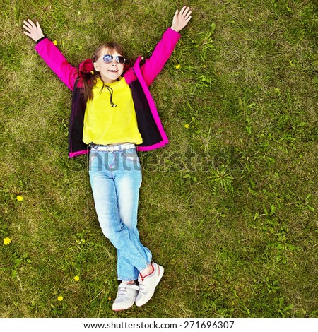 cheerful girl in sunglasses lying on the grass in the park. child outdoors. vacation in the summer park. top view - stock photo