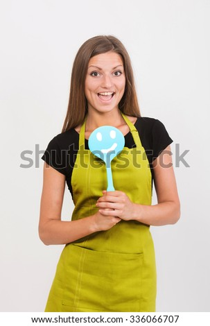 Cheerful girl in yellow apron with a smiley face spatula - stock photo