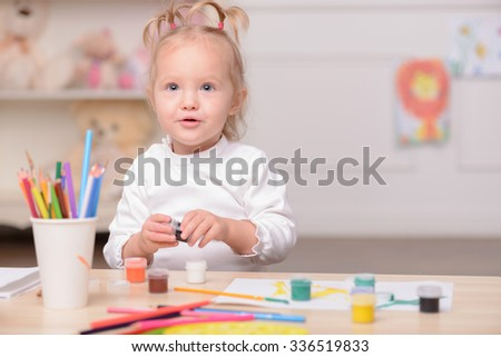 Cheerful girl is painting with joy. She is sitting at the desk and looking forward with interest. The girl is holding the paint. Copy space in right side - stock photo