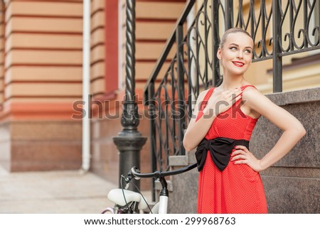 Cheerful girl is standing near her bicycle. She is looking aside happily and smiling. The lady is laying her arm on heart with love. Copy space in left side - stock photo