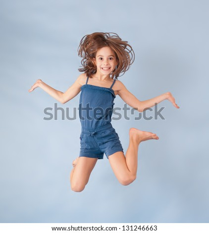 cheerful girl jumping on a blue background - stock photo