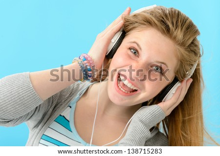 Cheerful girl listening to music with headphones - stock photo