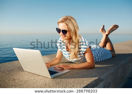 Cheerful girl lying at summer on the beach near sea and talks to her friends on the laptop via Wi Fi - stock photo