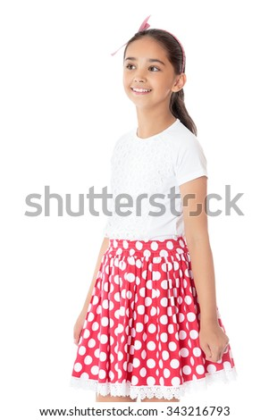 Cheerful girl of Eastern appearance with long dark curly hair, a short red and white polka dot skirt, posing for the camera. Closeup - Isolated on white background - stock photo