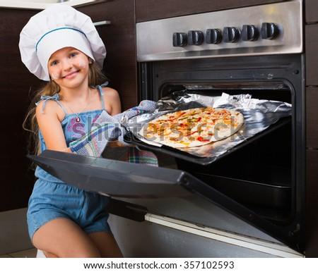 Cheerful girl prepared Italian pizza at home - stock photo