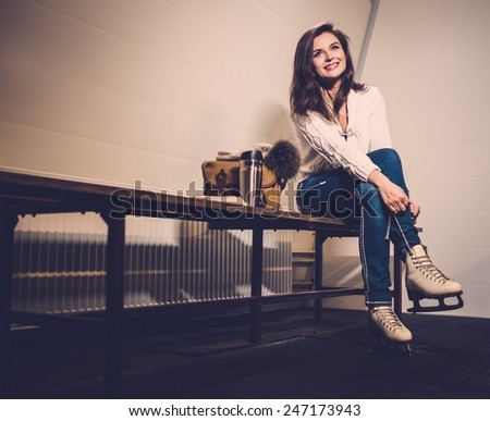 Cheerful girl putting on skates  in locker room - stock photo
