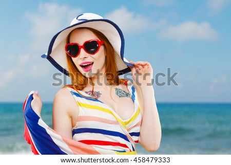 Cheerful girl with hat, striped dress and heart-shaped red sunglasses smiling widely and looking aside. Summer look. Against the background of the sea, head and shoulders - stock photo