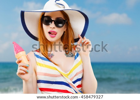 Cheerful girl with hat, striped dress and sunglasses holding ice-cream. Summer look. Against the background of the sea, head and shoulders - stock photo