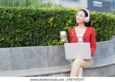 cheerful girl with laptops in park, chinese woman. - stock photo