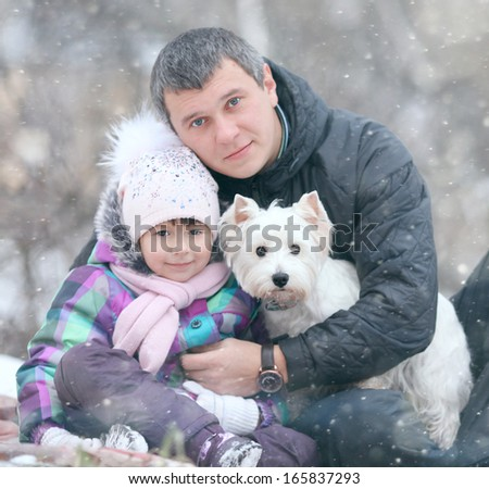 cheerful girl with my dad and little dog in winter park - stock photo