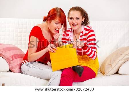 Cheerful girlfriends open letter while sitting on sofa  at living room - stock photo