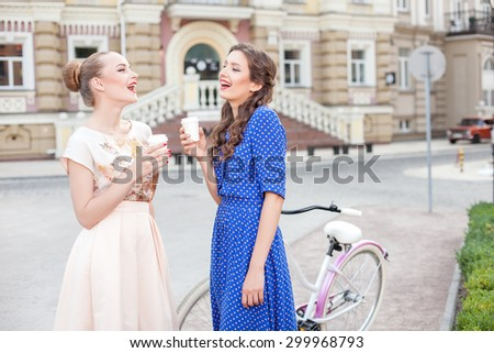 Cheerful girls are talking and drinking coffee in city. They are standing near bicycle. The friend are looking at each other with joy and laughing. Copy space in right side - stock photo
