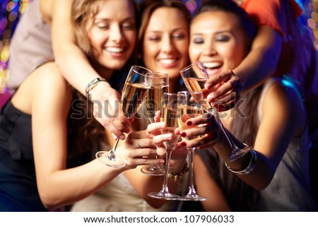 Cheerful girls clinking glasses of champagne at the party - stock photo