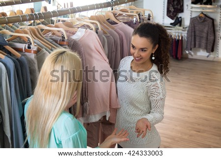 Cheerful girls looking for new garments at the store - stock photo