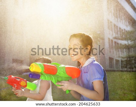 Cheerful girls playing water guns in the park - stock photo