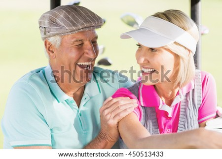 Cheerful golfer couple sitting in golf buggy - stock photo