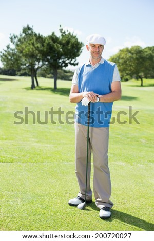 Cheerful golfer smiling at camera holding his club on a sunny day at the golf course - stock photo