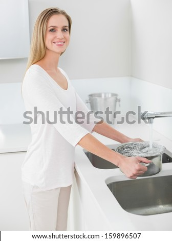 Cheerful gorgeous woman filling pan with water in bright kitchen - stock photo