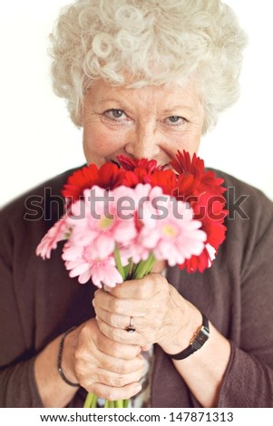 Cheerful grandmother happy to have received flowers on mother's day - stock photo