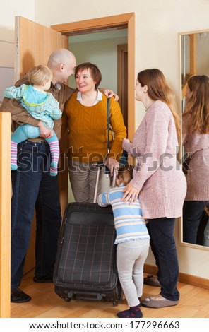 cheerful grandmother with luggage coming to family with two children home - stock photo