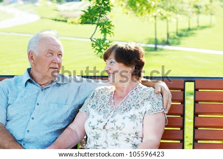 Cheerful grandparents sitting in park - stock photo