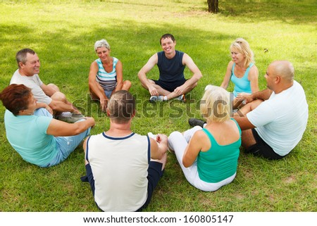 Cheerful group of adult people are sitting on the grass  - stock photo