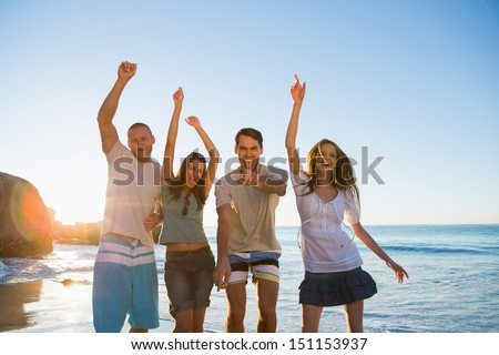 Cheerful group of friends dancing together on the beach - stock photo