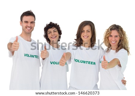 Cheerful group of volunteers giving thumbs up on white background - stock photo