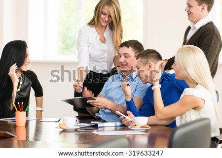 Cheerful  group of young business people in the office. Students at table - stock photo