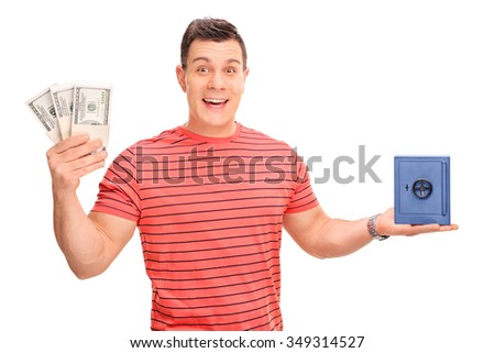 Cheerful guy holding few stacks of money and a small blue safe isolated on white background - stock photo