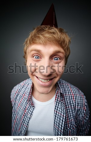 Cheerful guy in a cone cap being ready for fools day celebration - stock photo