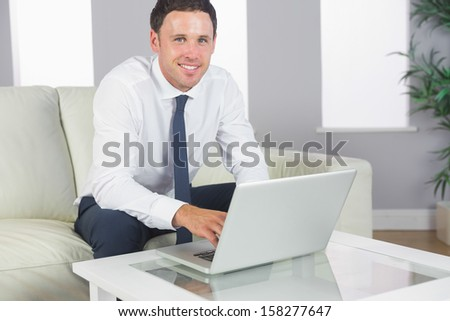 Cheerful handsome businessman working at laptop in bright living room - stock photo