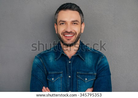 Cheerful handsome. Confident mature man in jeans shirt keeping arms crossed and smiling while standing against grey background - stock photo