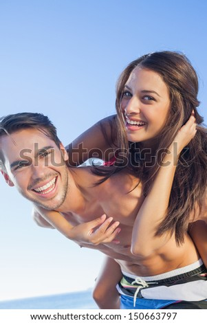 Cheerful handsome man carrying his girlfriend on his back on the beach - stock photo