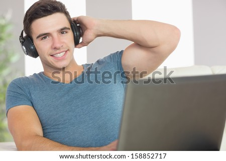 Cheerful handsome man using laptop listening to music in bright living room - stock photo