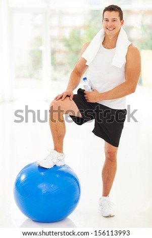 cheerful handsome young fitness man in gym - stock photo