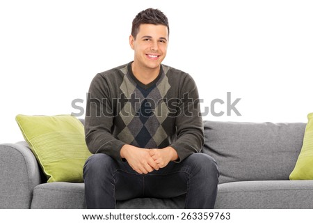 Cheerful handsome young man sitting on a modern grey sofa with green pillows isolated on white background - stock photo