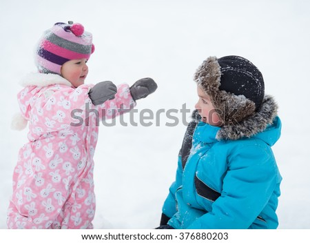 cheerful happy boy ahd baby girl playing in winter park, outdoor - stock photo