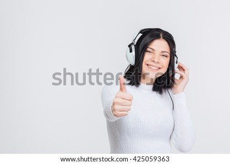 Cheerful happy brunette girl listening music in headphones and thumbs up, isolated on white background - stock photo