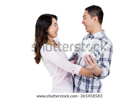 Cheerful happy couple holding money while standing against white background - stock photo