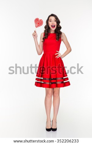 Cheerful happy excited curly young woman in red dress holding heart shaped lollipop - stock photo