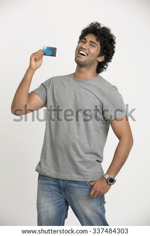 Cheerful happy Indian young man showing credit card on white. - stock photo